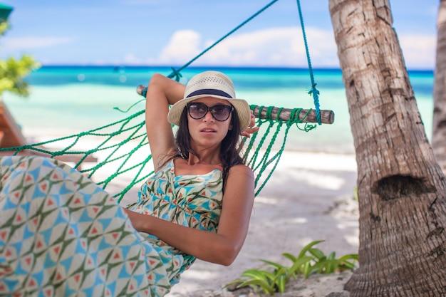 Jonge vrouwenzitting bij hangmat in de schaduw van de boom op een strand