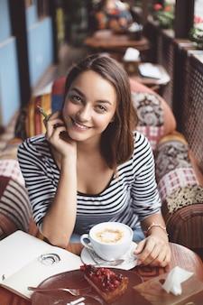 Jonge vrouwenzitting binnen in stedelijke koffie