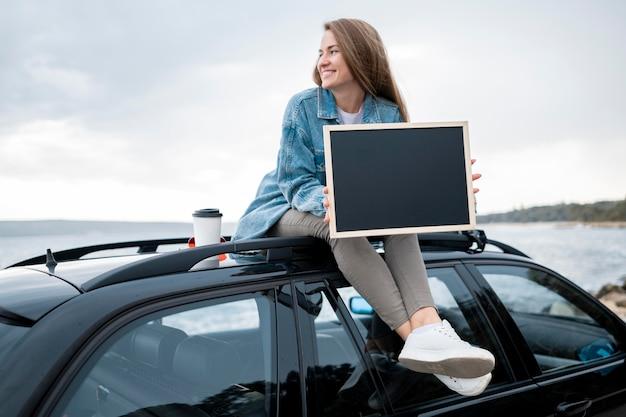 Jonge vrouwenzitting bovenop de auto