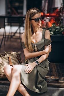 Jonge vrouwenzitting buiten het koffie