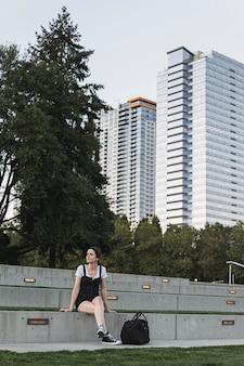 Jonge vrouwenzitting en gebouwen op achtergrond