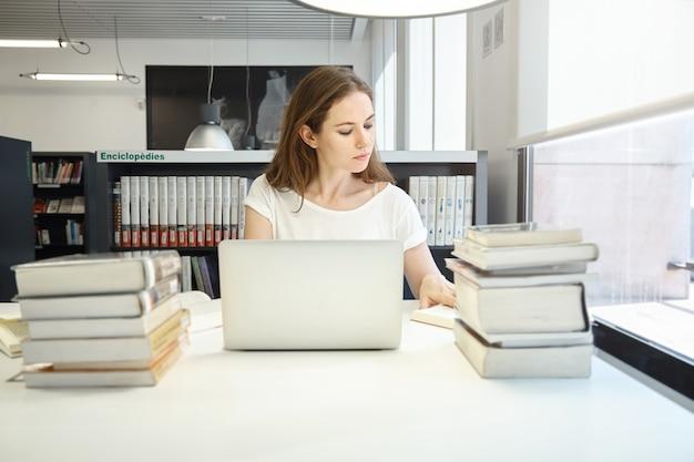 Jonge vrouwenzitting in bibliotheek met laptop