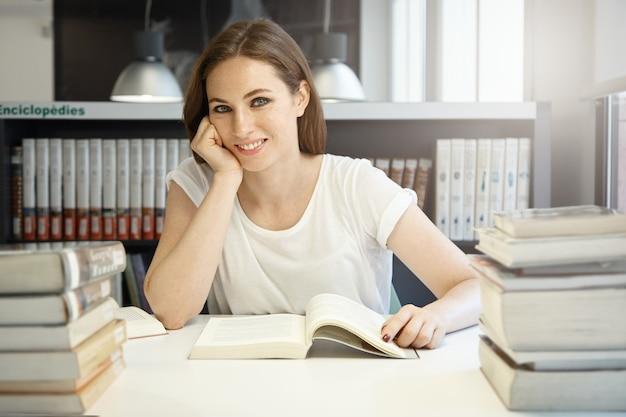 Jonge vrouwenzitting in bibliotheek
