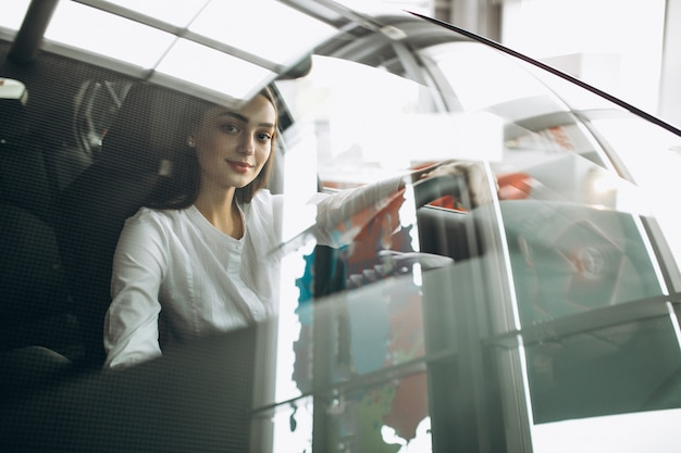 Jonge vrouwenzitting in een auto in een autotoonzaal