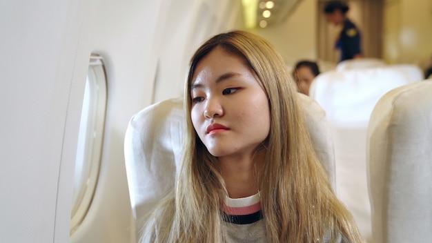 Jonge vrouwenzitting in een vliegtuig