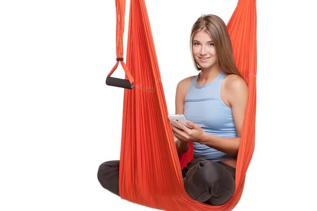 Jonge vrouwenzitting in hangmat voor antizwaartekracht luchtyoga