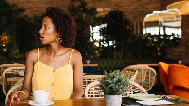 Jonge vrouwenzitting in het restaurant die weg eruit zien