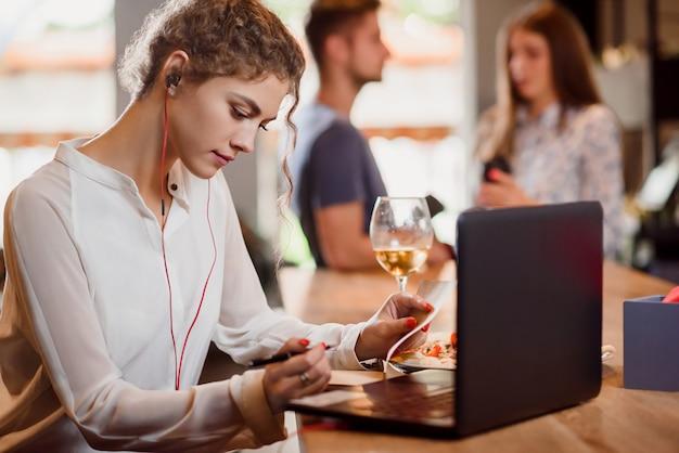 Jonge vrouwenzitting in koffie en het werken met notitieboekje.