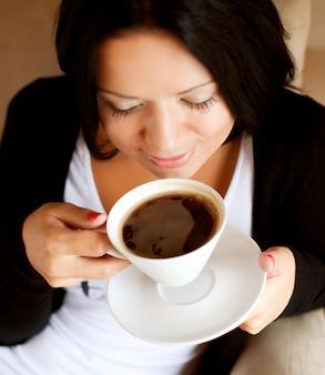 Jonge vrouwenzitting in koffie het drinken koffie