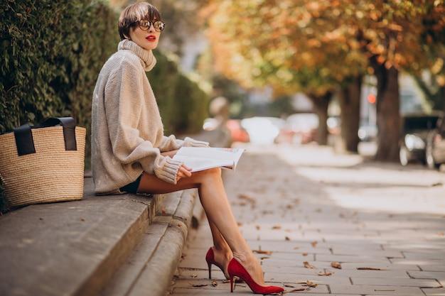 Jonge vrouwenzitting in park en lezing