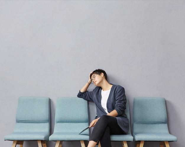 Jonge vrouwenzitting in wachtkamer