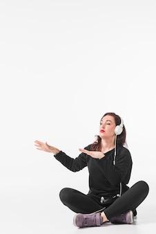 Jonge vrouwenzitting met gekruist been die van muziek bij hoofdtelefoon het dansen genieten