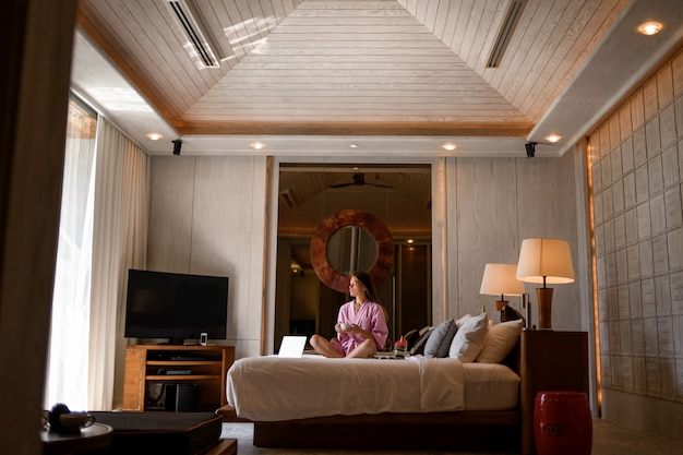 Jonge vrouwenzitting met kop van koffiebed in modern slaapkamerbinnenland met, tv, laptop en andere manierdecoratie. moderne slaapkamer. ontspanning na werkdagen. bluetooth-teken