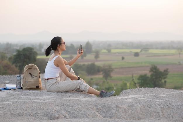 Jonge vrouwenzitting met mobiele telefoon. hooggebergte toeristenpad bij zonsondergang.