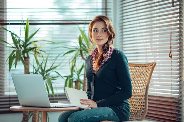 Jonge vrouwenzitting naast laptop met een boek