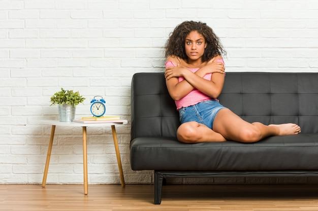 Jonge vrouwenzitting op de bank die koud wegens lage temperatuur of een ziekte gaan