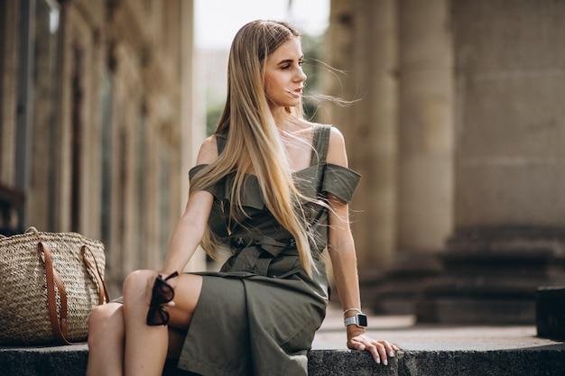 Jonge vrouwenzitting op de treden van een oud bvgebouw