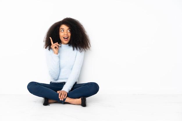 Jonge vrouwenzitting op de vloer die een idee denkt die de vinger benadrukt
