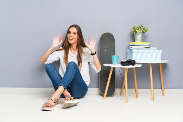 Jonge vrouwenzitting op de vloer die een ok teken met vingers toont