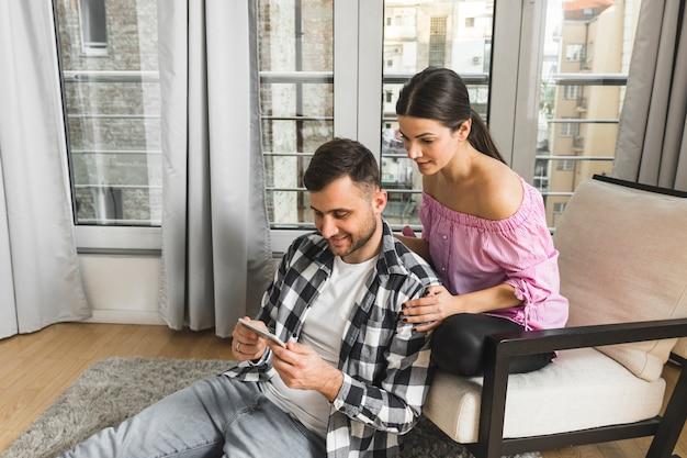 Jonge vrouwenzitting op stoel die haar vriend thuis bekijkt die mobiele telefoon met behulp van