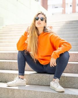 Jonge vrouwenzitting op treden met vrijetijdskleding