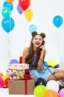 Jonge vrouwenzitting op vloer lachen en op telefoon spreken