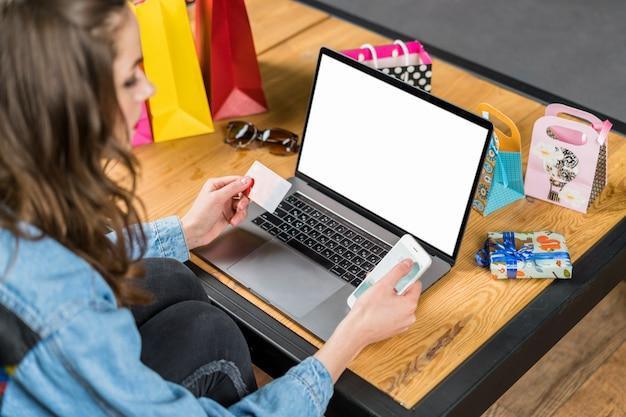 Jonge vrouwenzitting voor laptop met het lege scherm die mobiele telefoon en creditcard in hand houden