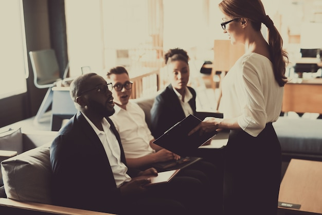 Jonge vrouwmanager legt bedrijfsidee uit aan team.