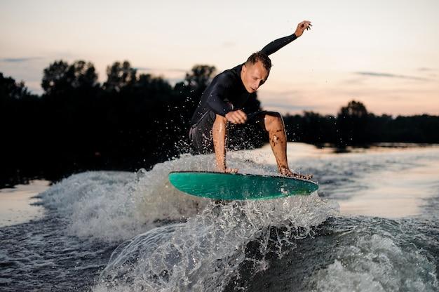 Jonge wakesurfer in zwarte zwembroek springen op een wake board