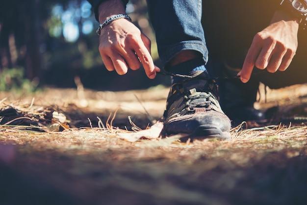 Jonge wandelaar bindt de veters op zijn schoen tijdens een vakantie backpacking in het bos.
