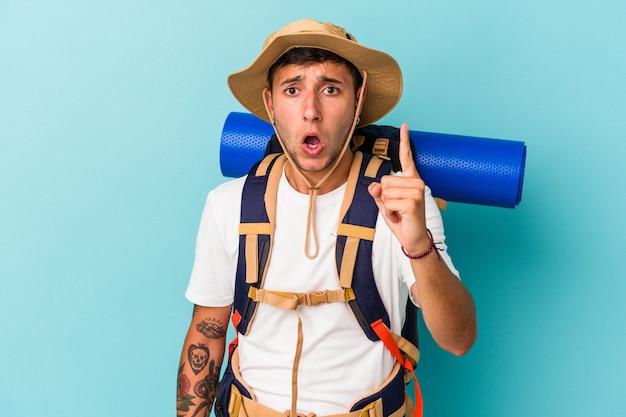 Jonge wandelaar man met hoed geïsoleerd op blauwe achtergrond met een idee, inspiratie concept.