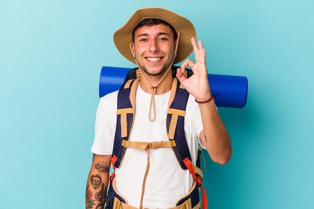Jonge wandelaar man met hoed geïsoleerd op blauwe achtergrond vrolijk en zelfverzekerd weergegeven: ok gebaar.