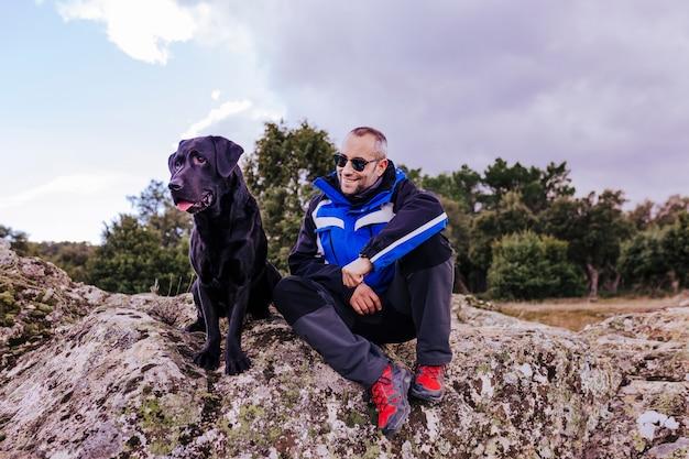 Jonge wandelaar man op de berg met zijn zwarte labrador op de top van een rots. bewolkte winterdag