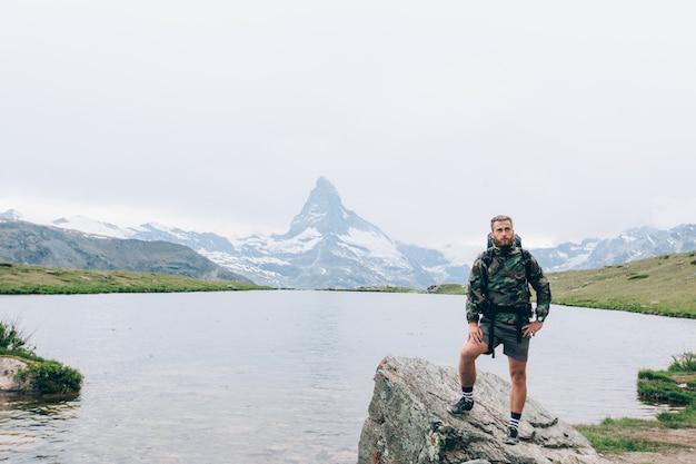 Jonge wandelaar rust naast een meer in de alpen van zwitserland. naast de berg matterhorn