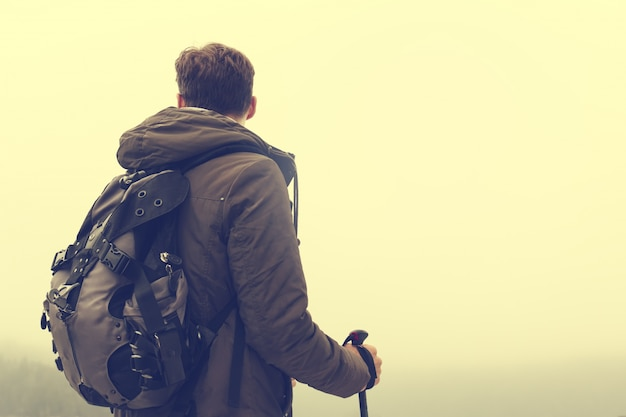 Jonge wandelende man sportman of reiziger met rugzak verblijven en kijken naar horizon. toning.