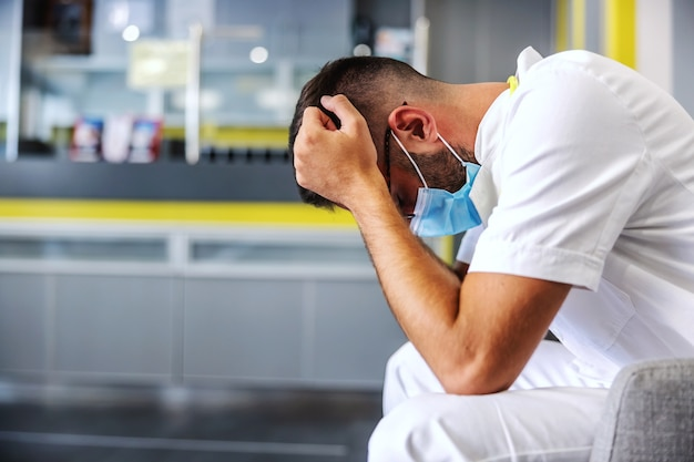 Jonge wanhopige dokter zit in de gang en wordt angstig omdat zijn patiënt erg ziek is Premium Foto
