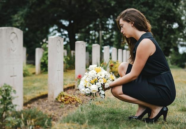 Jonge weduwe die bloemen legt bij het graf