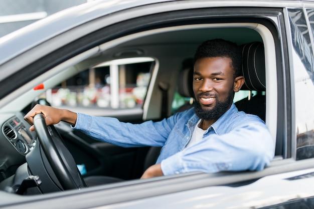 Jonge welvarende succesvolle zakenman zijn nieuwe dure auto rijden met vertrouwen en trots