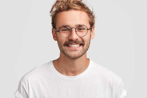 Jonge welvarende zakenman met krullend haar, stralende glimlach, blij om succes in het leven te behalen, gekleed in een wit t-shirt, geniet van een vrije dag thuis met familie