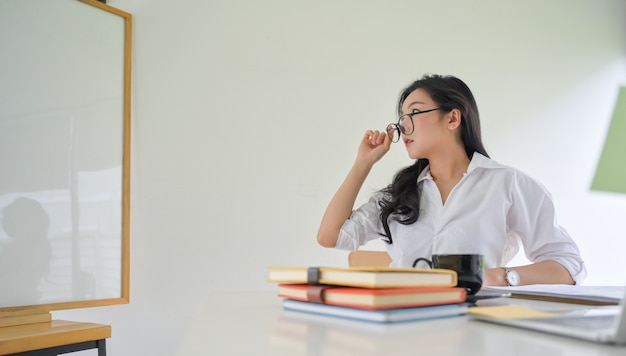 Jonge werkende vrouw met bril en kijken naar het witte bord in het kantoor.