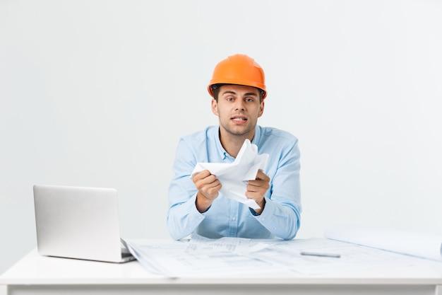 Jonge werkman geërgerd boos in woedend gebaar. negatieve uitdrukking op wit grijze achtergrond.