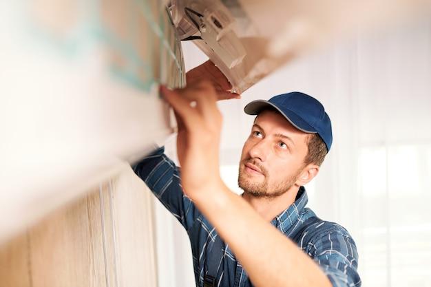 Jonge werkman in werkkleding die systeem van airconditioner onderzoekt om de reden van wanorde te achterhalen