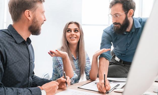 Jonge werknemer aan haar collega's die haar ideeën uitleggen. het concept van teamwerk