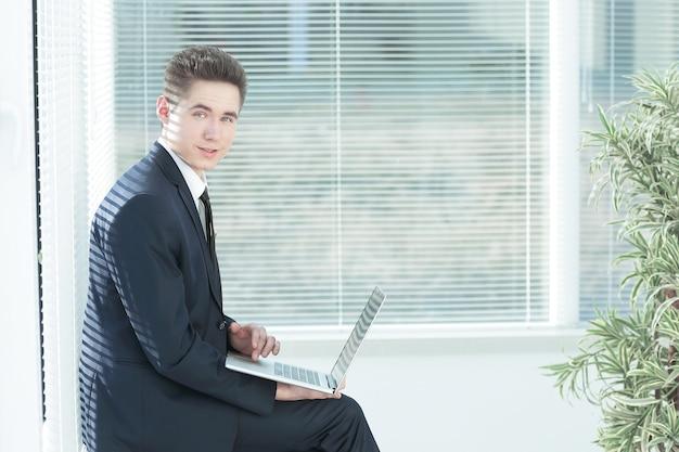 Jonge werknemer die aan een laptop werkt die in de gang van de office.photo zit met kopieerruimte