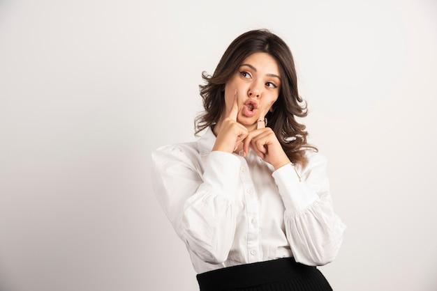 Jonge werknemer die haar mond op wit houdt.