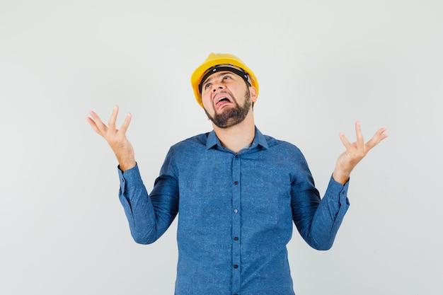 Jonge werknemer die hulpeloos gebaar toont, tong in overhemd, helm uitsteekt en verward kijkt.