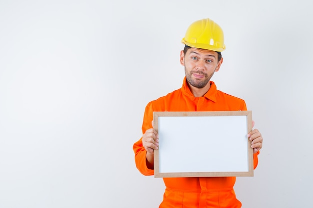 Jonge werknemer die in eenvormig leeg frame houdt en vrolijk kijkt.