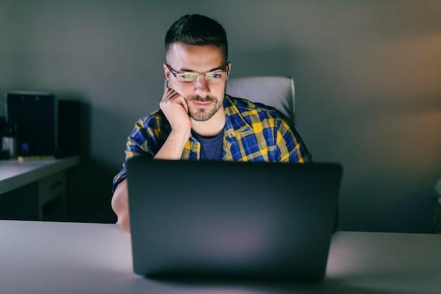 Jonge werknemer die laptop met behulp van terwijl het leunen op hand terwijl het zitten in het bureau laat bij nacht