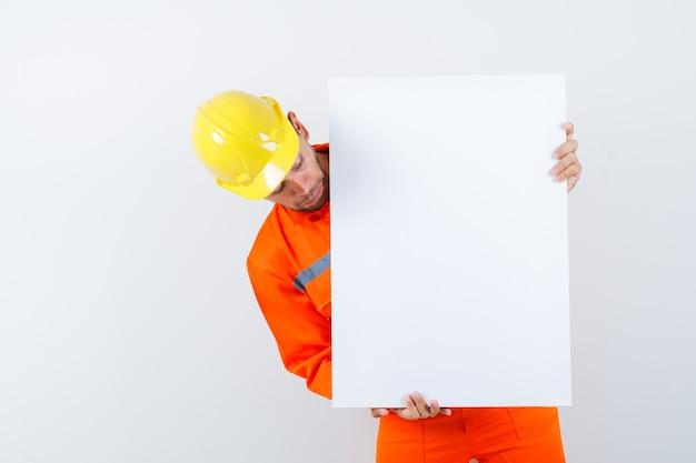 Jonge werknemer die leeg canvas in uniform, helm bekijkt en gericht kijkt.