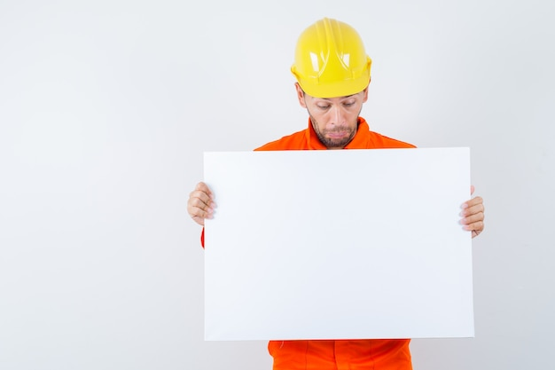 Jonge werknemer die leeg canvas in uniform, helm bekijkt en verbaasd kijkt.